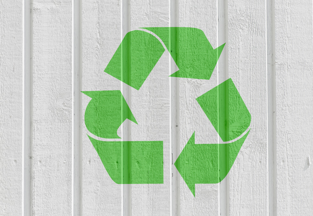 Recycling symbol on white wooden wall background