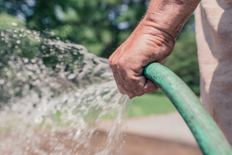 man holding a water hose