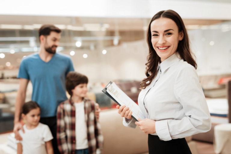 sales clerk smiling with customers behind her